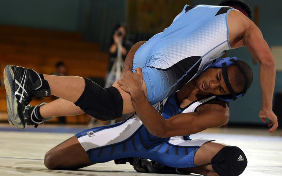 Eric Bush of Seoul American lifts Mark Tortillas of Osan American in a head-in-arm hold during Saturday's 129-pound bout in a DODDS-Korea wrestling tri-meet at Seoul American High School, South Korea. Bush superior decisioned Tortillas 2-0 (7-0, 8-2) and Seoul American won the dual meet, 41-6.