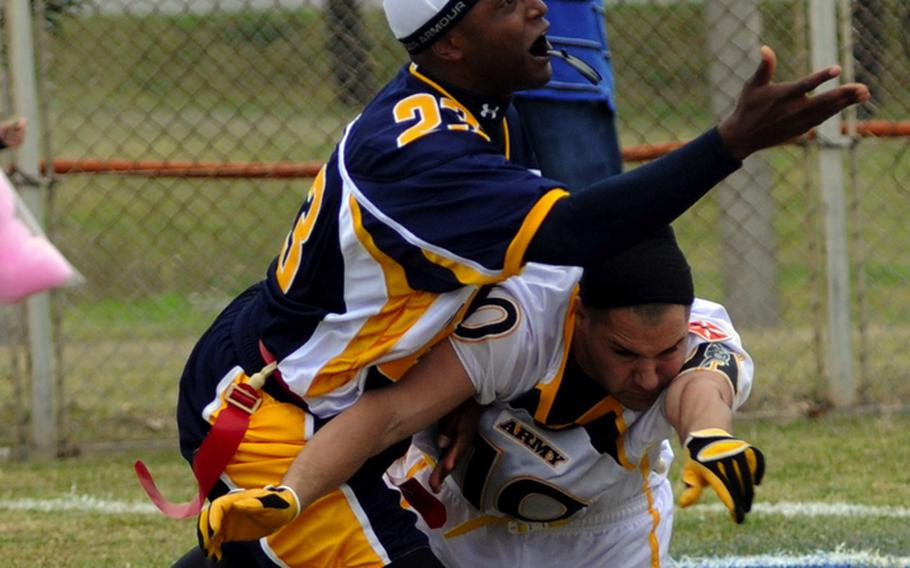 Navy's Antoniio Johnson, left, tries to recover a ball he knocked loose from Army's Brian Arthur during Saturday's Army-Navy flag football game at Torii Field, Torii Station, Okinawa. The play was ruled a safety, cutting Army's lead to 3-2, and it proved to be the turning point as Navy broke a six-year losing streak in the 21-year-old series, beating Army, 27-3.