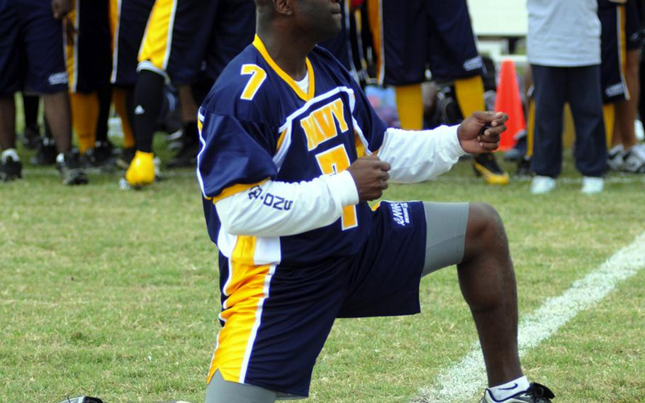 Navy quarterback Robert Trisby feigns gunfire at his Army opponents during lineup introductions prior to Saturday's Army-Navy flag football game at Torii Field, Torii Station, Okinawa. Navy broke a six-year losing streak in the 21-year-old series, beating Army, 27-3.