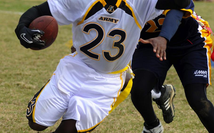 Army running back Joseph Smallwood tries to avoid the flag tackle of Navy's Antonio Johnson during Saturday's Army-Navy flag football game at Torii Field, Torii Station, Okinawa. Navy broke a six-year losing streak in the 21-year-old series, beating Army, 27-3.