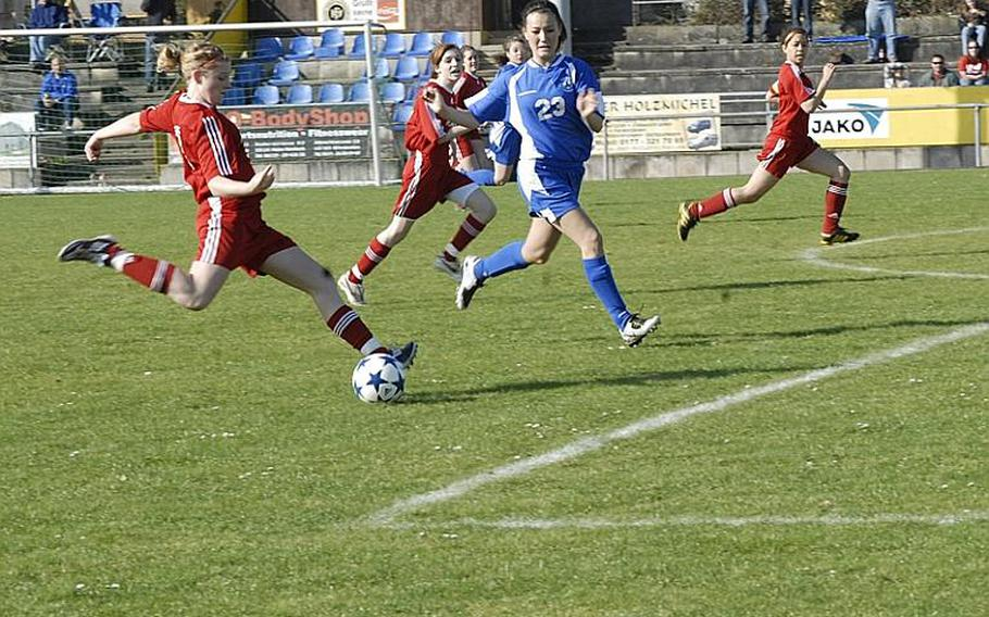 Kaiserslautern junior Emily Crawford takes a shot on goal as Wiesbaden junior Michelle Schonberg tries to stop her in a match at the Stadion In der Witz in Mainz-Kastel, Germany. The Lady Raiders won the match, 5-3.