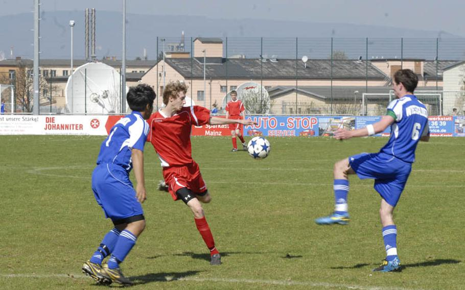 Kaiserslautern sophomore striker Cody Tremaine shoots between Wiesbaden seniors Alexander Hernandez, left, and Jeffrey Holt  at the Stadion In der Witz in Mainz-Kastel, Germany.  Tremaine scored the only goal for the Raiders, who ended the match in a 1-1 draw with Wiesbaden.