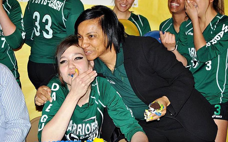 Daegu American senior four-time All-Far East spiker Kristina Bergman gets an embrace from her coach Joanna Wyche after signing a national letter of intent to attend the University of Central Oklahoma, an NCAA Division II school. The signing ceremony was held before teammates, her stepfather Charles Phillips and her mother Yong Phillips, Wyche, classmates, school administration, 19th Theater Sustainment Command's commanding general Brig. Gen. Thomas A. Harvey and Command Sgt. Maj. Brian S. Connie.