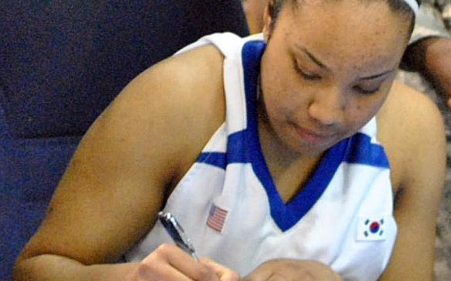 Senior guard Jordan Elliott of the two-time Far East Division I Tournament champion Seoul American Falcons signs a national letter of intent to play basketball for the U.S. Military Academy at West Point, N.Y.