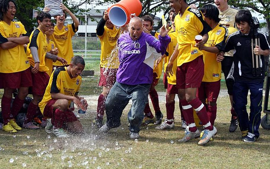 Matthew C. Perry  boys soccer coach Mark Lange gets the traditional water-bucket shower to the amusement of his players after Saturday's championship match in a six-team DODDS Japan regular-season tournament at Matthew C. Perry High School, Japan. Perry blanked Nile C. Kinnick, 1-0, and ran its school-best regular-season record to 14-1-1.