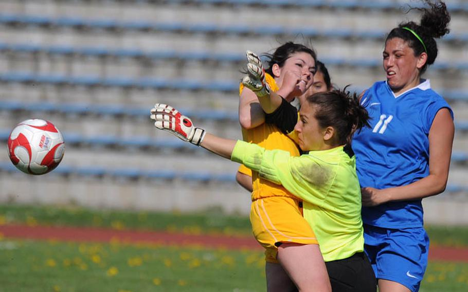 Baumholder goalie Rachel Krahn knocks the ball out of the danger zone in front of teammate Laura Bailes, left, and Ramstein's Makenzie Crews. Krahn's efforts were for naught on Saturday as the Ramstein beat Baumholder, 7-0.