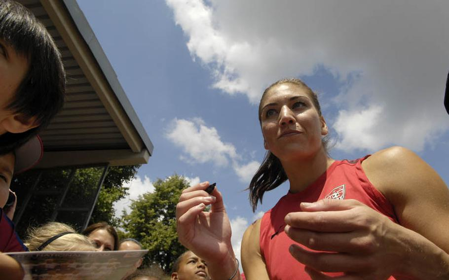 Hope Solo, the U.S. Women's National Team goalkeeper, signs autographs after Thursday's practice session at SG Kirchheim soccer field in Heidelberg, Germany, before the team's second 2011 World Cup game against Colombia. Many local U.S. military members and their families were invited to watch the practice session.