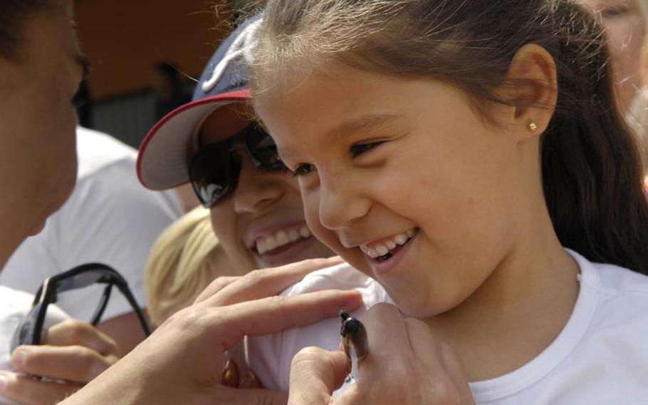 Six-year-old Camila Ramirez gets her T-shirt autographed by Hope Solo, the U.S. Women's National Team goalkeeper after Thursday's soccer practice at SG Kirchheim soccer field in Heidelberg, Germany. Camila's father is a U.S. Army warrant officer stationed in Stuttgart, Germany.
