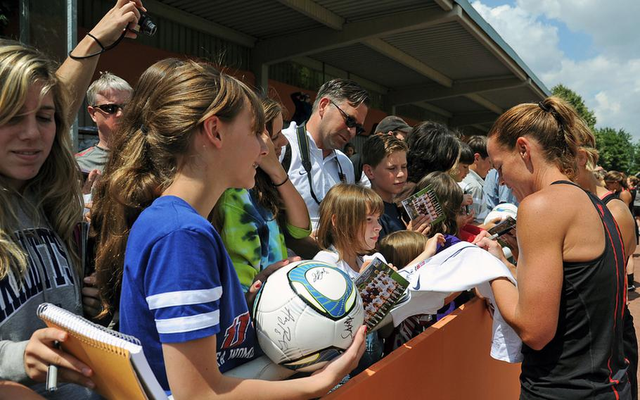 Christie Rampone, right, and other members of the U.S. women's national soccer team sign autographs Thursday following an open practice session in Heidelberg, Germany. The practice was attended by hundreds of members of the American military communities. The women play their second game of the World Cup against Colombia on Saturday in Sinsheim.