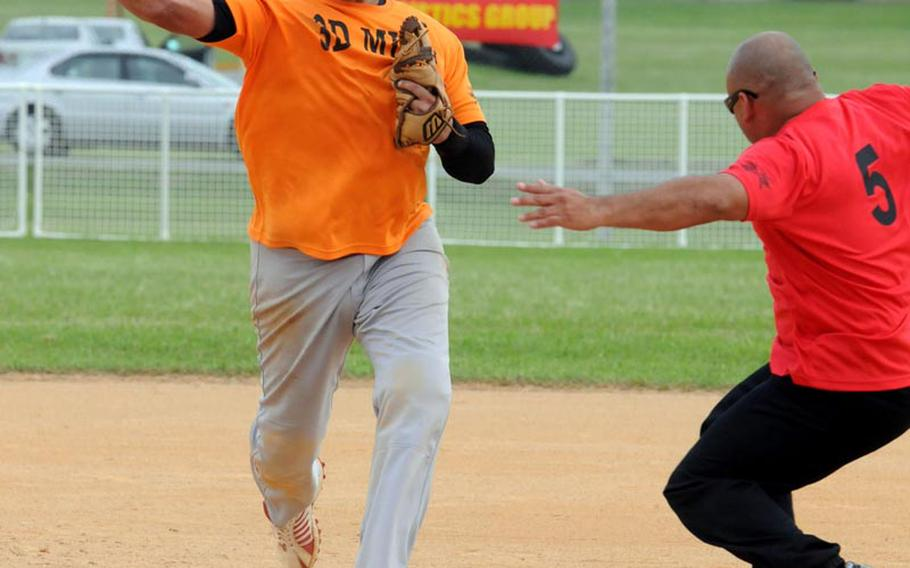 Second baseman Francisco Poo of 3rd Marine Logistics erases Marine Corps Base Camp S.D. Butler runner Jesse Segura and makes the relay throw to first base during Friday's championship-bracket final game in the double-elimination playoffs in the 2011 Marine Corps Far East Regional Softball Tournament at Field 1, Gunners Fitness & Sports Complex, Camp Foster, Okinawa. 3rd MLG won 7-6 in nine innings, then beat Base again 11-9 in Friday' evening's championship game, winning the title for the second straight year.