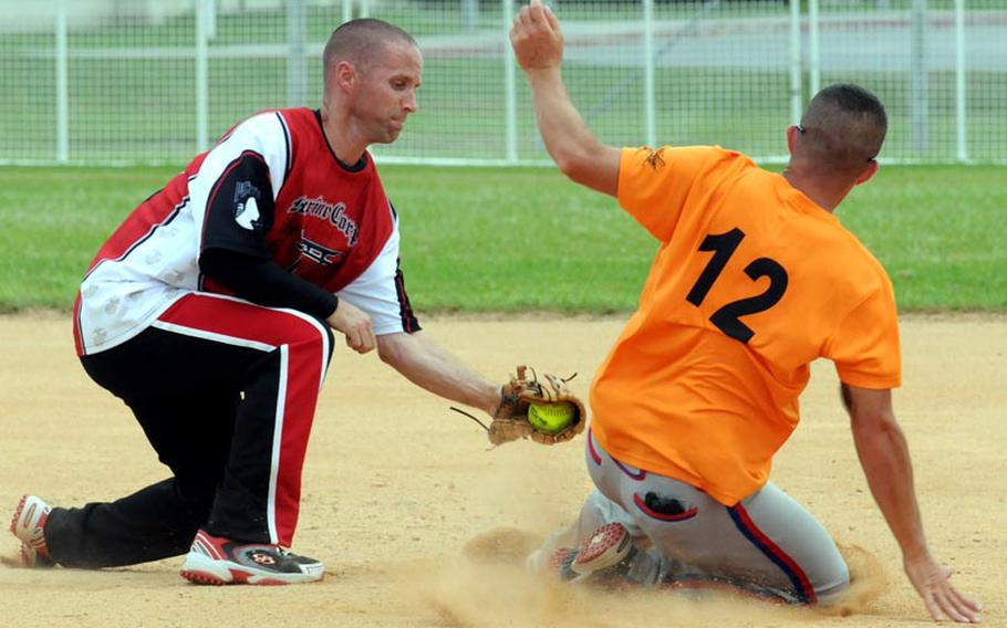 Marine Corps Base Camp S.D. Butler shortstop Thomas Meinhart applies the tag to 3rd Marine Logistics Group baserunner Daniel Polk during Friday's championship-bracket final game in the double-elimination playoffs in the 2011 Marine Corps Far East Regional Softball Tournament at Field 1, Gunners Fitness & Sports Complex, Camp Foster, Okinawa. Polk was ruled safe on the play. 3rd MLG won 7-6 in nine innings, then beat Base again 11-9 in Friday' evening's championship game, winning the title for the second straight year.