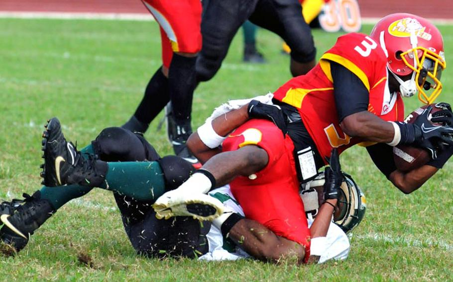 Foster Bulldogs running back Nekory Moorer (3) is tackled by Joint Task Force Wolfpack defender John Butler during Saturday's U.S. Forces Japan-American Football League South Division title game.
