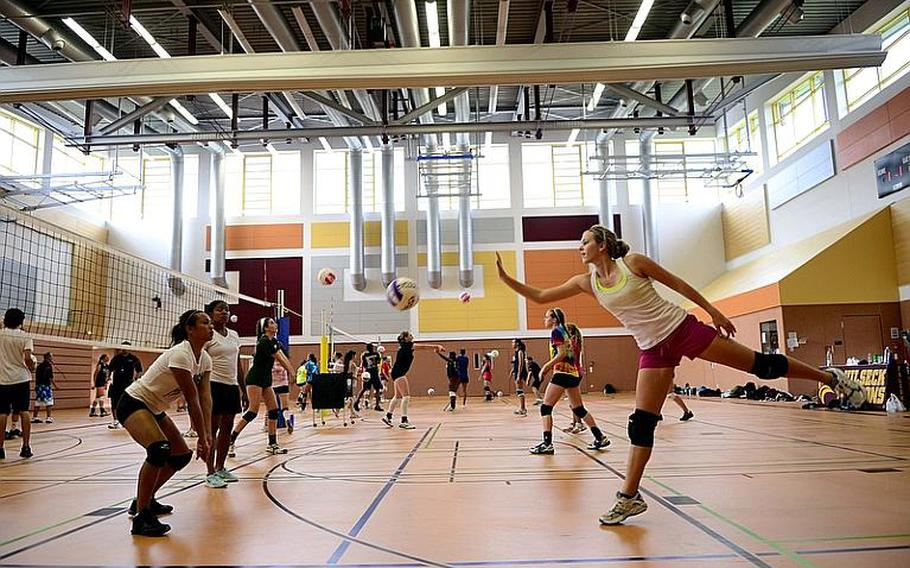 Abby Diaz, 17, and Rachel Hutchinson, 17, seniors from Patch High School, Stuttgart, Germany, practice a drill Monday at this year's DODDS-Europe volleyball camp at Vilseck High School.