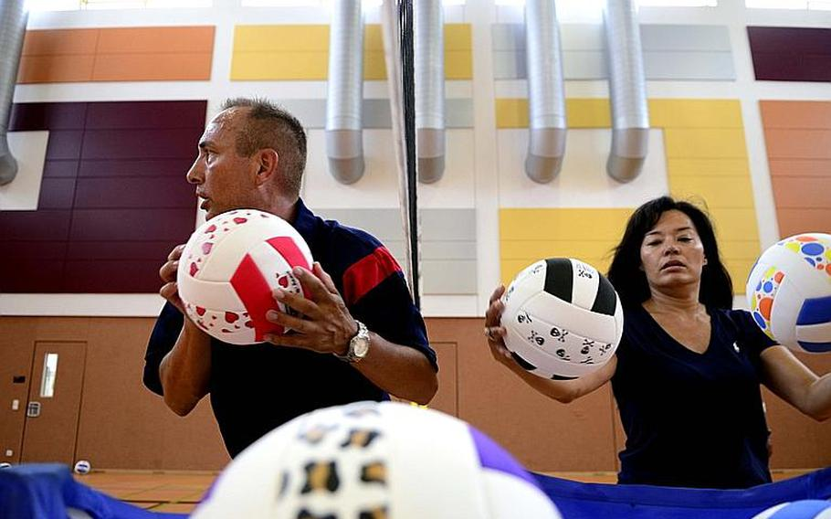 Coach John Kohut, a physical education teacher from Stuttgart, Germany, runs passing and footwork drills while Tina Juliano, a volleyball mom and volunteer from Vicenza, Italy, shags balls at this year's DODDS-Europe volleyball camp at Vilseck High School .