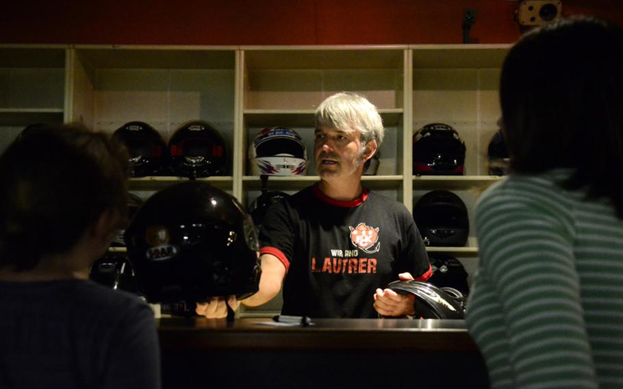 Gerald Conrad, co-owner of Go! Indoor-Kart, hands out helmets to customers before they get behind the wheel.