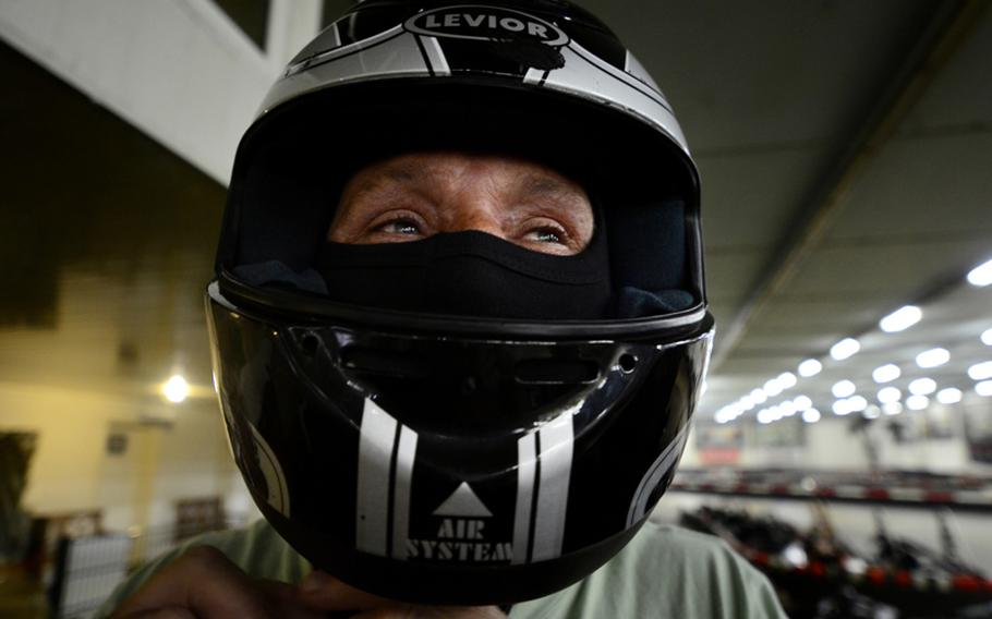 Peter Zuidhoek, of Voorhout, Netherlands, fastens the chin strap of his helmet before racing his son at the Go! Indoor-Kart track.
