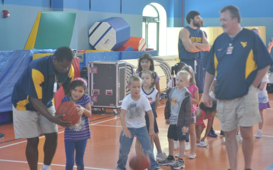 West Virginia head coach Bob Huggins, right, watches associate head coach Larry Harrison direct a line of base kids during a clinic Wednesday put on by coaches and players of West Virginia and Illinois at Aviano Air Base, Italy.