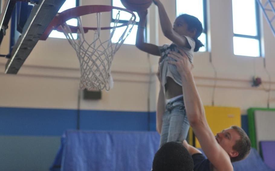 West Virginia basketball player Kevin Noreen gives Maya Dixon, 6, a boost during a clinic Wednesday at Aviano Air Base, Italy, put on by players and coaches from the universities of West Virginia and Illinois.
