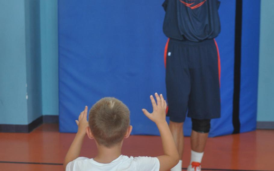 Illinois center Meyers Leonard takes part in a passing drill with Tristen Karinshak, 6, during a clinic Wednesday at Aviano Air Base in Italy put on by players and coaches from the universities of Illinois and West Virginia.