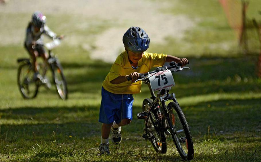 Jeison Huerta, 8, pushes his bike up a steep section of the Fat Tire Spectacular Mountain Bike Race in Garmisch, Germany, with his sister Ana Maria, 10, not far behind.