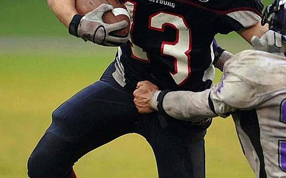 Bitburg's Kyle Edgar keeps a Mannheim player at arms length as he picks up yardage in last season's championship game.