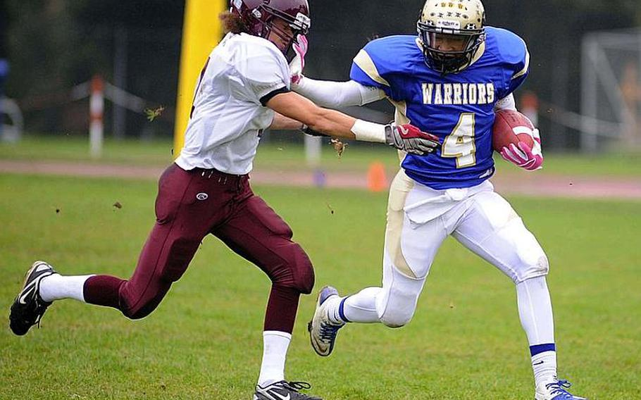 Wiesbaden's Daniel Harris, right, straight arms Vilseck's Darius Whitehead on his way to a big gain in a Division I-South matchup in Wiesbaden last season.