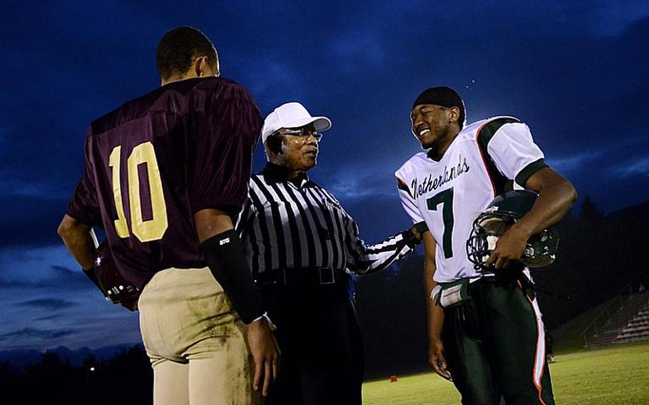Ben McDaniels of Baumholder and J. D. Pollock of AFNORTH, meet with referee Tomas Villegas Jr. just before the second half of play Friday night at  Baumholder, Germany.