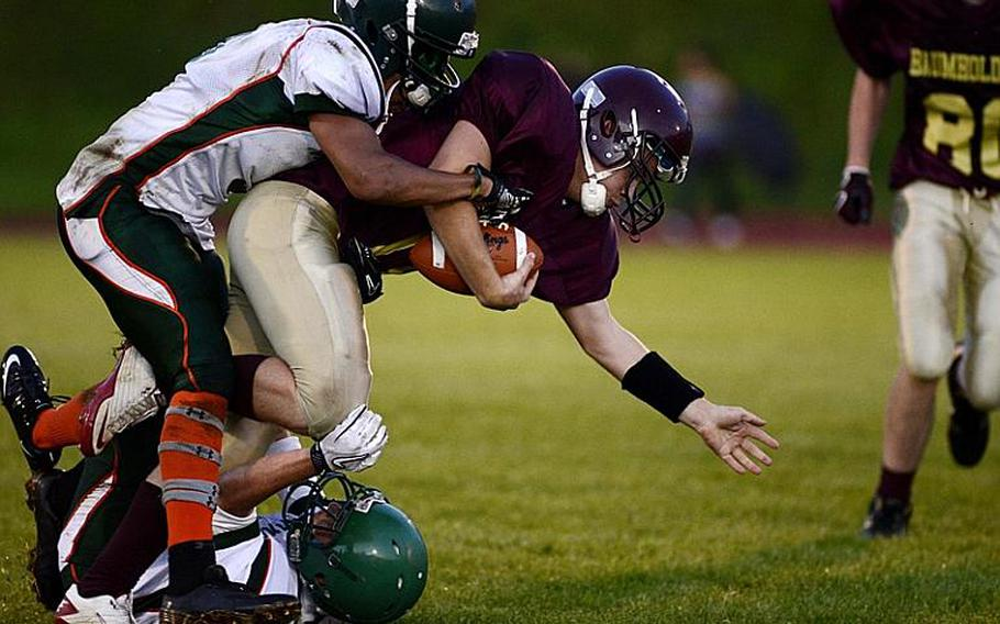 Christian Kubas, a sophomore quarterback for Baumholder, is tackled by two AFNORTH players, Friday night at Baumholder, Germany.