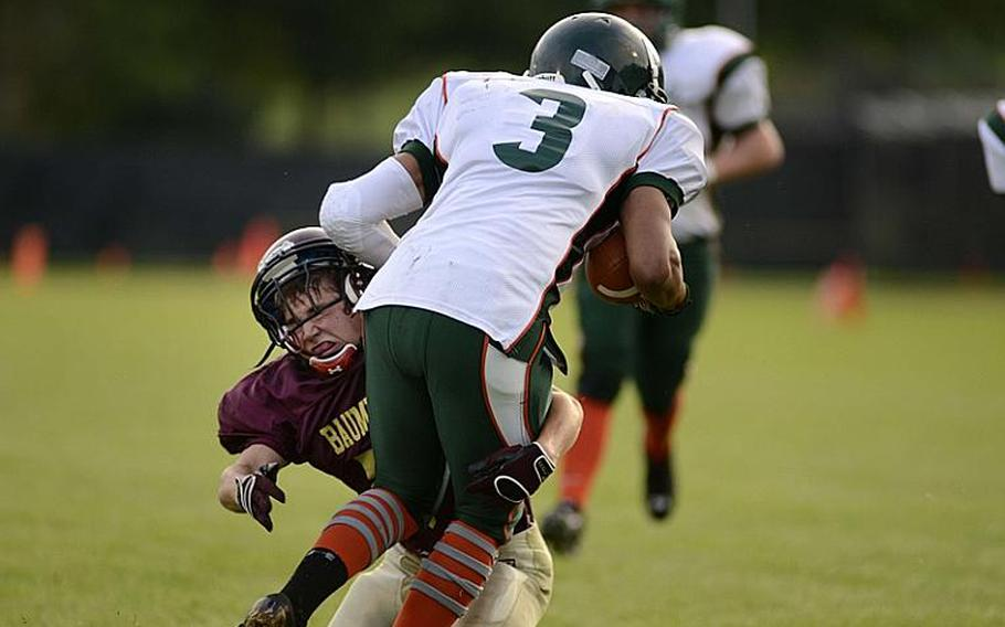 Dante Brown, a junior running back for the AFNORTH Lions, is tackled by Ben Holliday, a junior from the Baumholder Buccaneers, Friday night at  Baumholder, Germany.