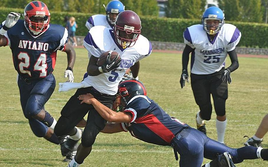 Schweinfurt running back Devontay Collier shrugs off the tackle of Aviano's Nik Weisner to pick up some yardage Saturday in his school's first ever football game. Collier, a junior, ran for 120 yards, but the Razobacks lost to the Saints, 37-7.