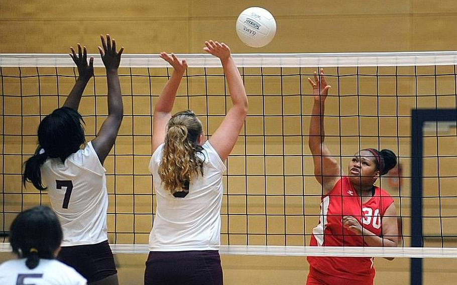 Kaiserslauterns Kalynn Richardson, right, knocks the ball back over the net against Baumholder's Joella Milledge, left, and Charlee Schroeder. The two teams won one a game apiece at the jamboree in Wiesbaden, on Saturday. Baumholder took the first game 25-19 and dropped the second 24-20 in the 35-minute match.