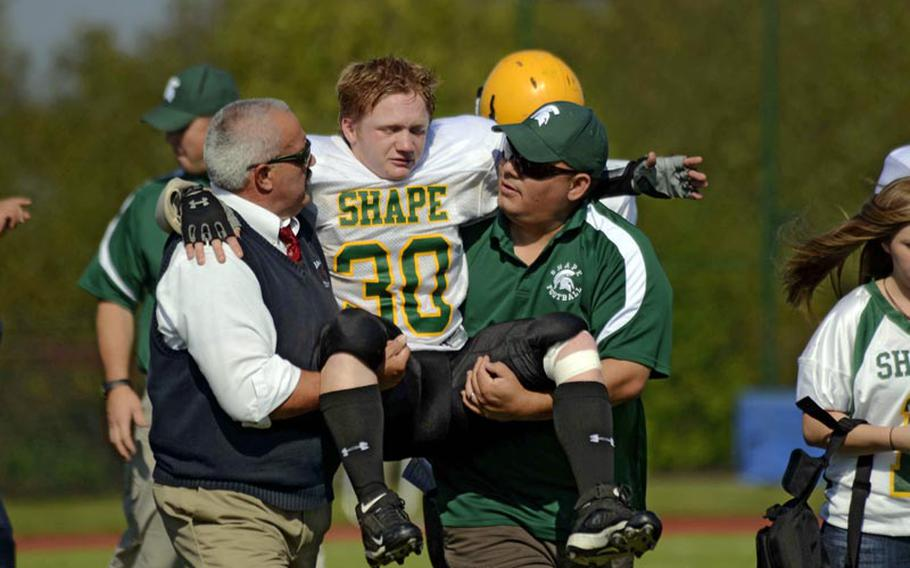 SHAPE's David Brackett is carried off the field after hurting his knee during the Spartans' loss to Bitburg Saturday.