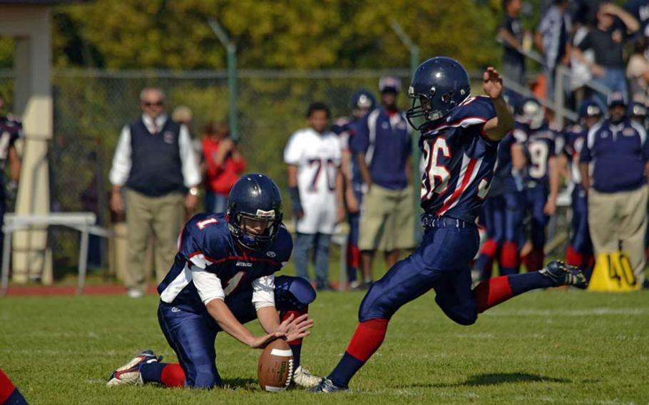 Bitburg's quarterback, Evan Less, holds the football for Christian Diaz's extra point attempt Saturday.
