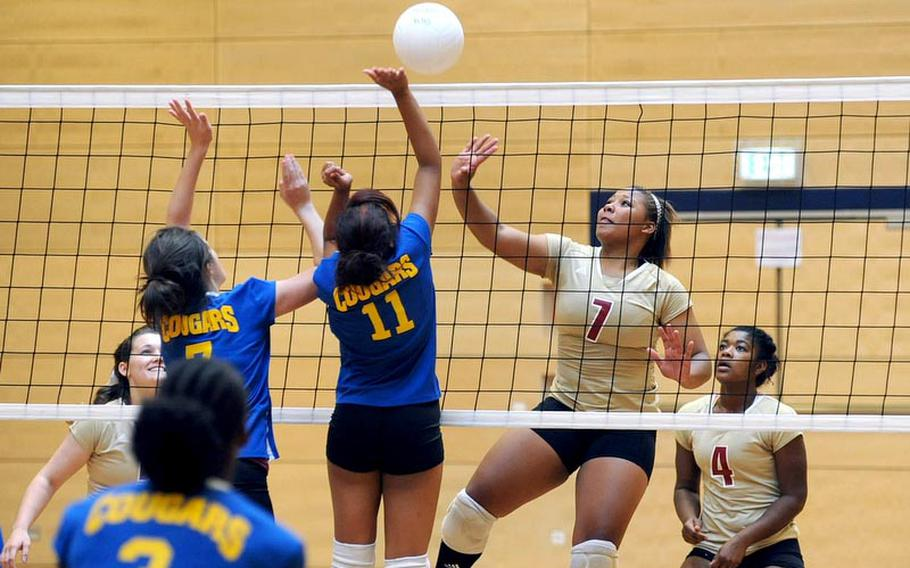Ansbach's Dani Miller and Akira James, from left, try to block a return by Vilseck's Deraj McClinton in a match in Wiesbaden on Saturday. Vilseck won 25-18, 25-13, 25-18. At right is Mariah Morris.