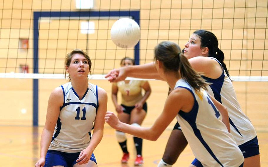 Wiesbaden's Annette Hutzky, right, gets to the ball in front of teammates Kaitlyn Velsaag, left, and Meghan Smith. Wiesbaden dropped their match against defending Division I champ Vilseck, at home Saturday, 19-25, 17-25, 20-25.