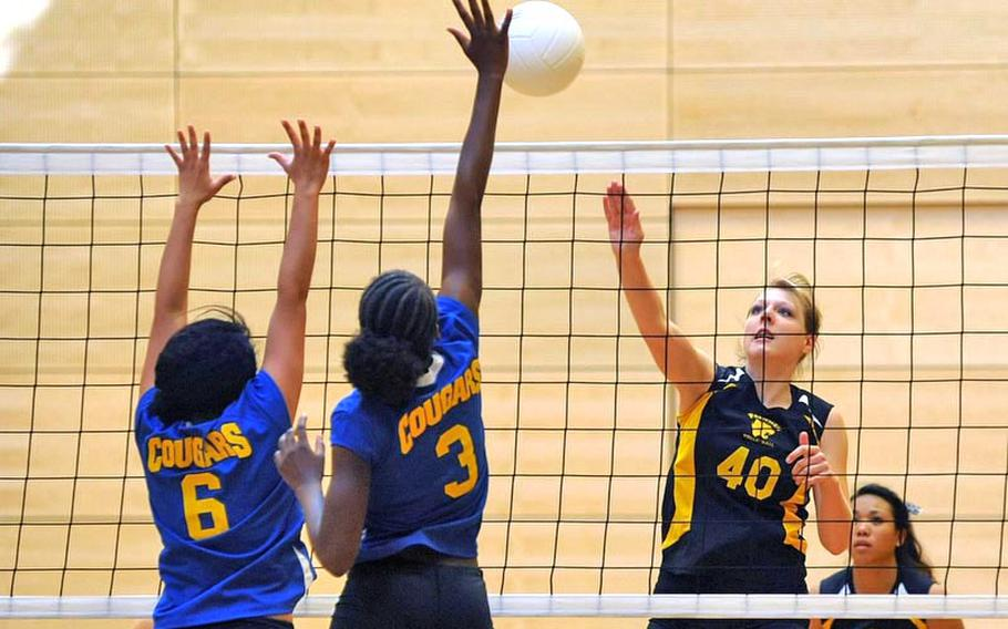 Patch's Elizabeth Derner, right, knocks the ball across the net against Ansbach's Jasmine Rodriguez, left, and Jahkaya Smith. Patch won the match in Wiesbaden on Saturday 25-10, 21-25, 25-16, 25-23.