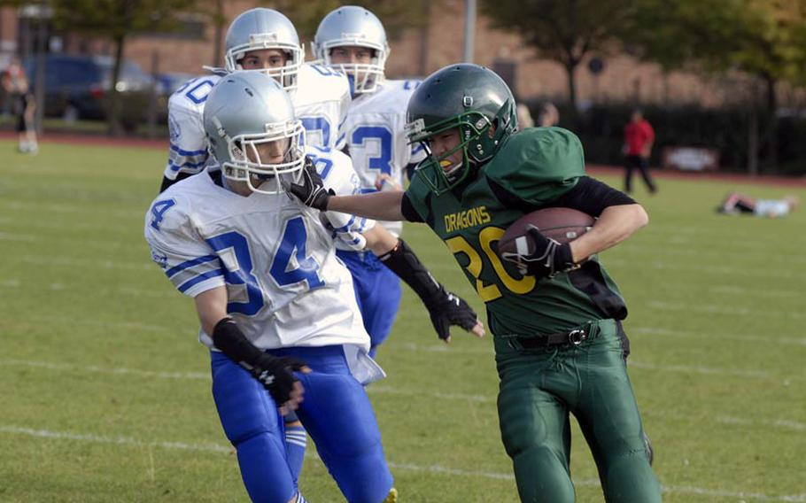 Alconbury running back Keith Marasigan, a junior, stiff arms Brussels defender Will Cole, sophomore, on his way to a 58-yard touchdown run, Saturday 24, at RAF Alconbury in England. The Dragons won the game 44-6.