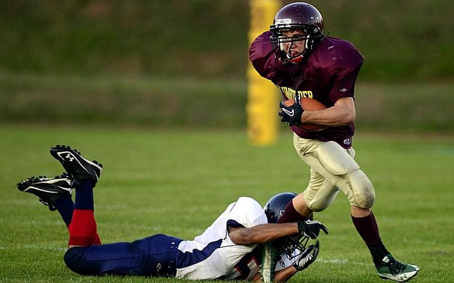 Baumholder's Ben Holliday slips out of the hands of Bitburg's Thomas Collins.