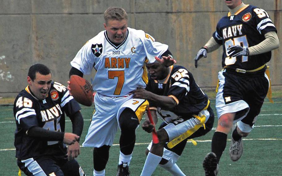 Army quarterback Jeremy Finney is tackled by Navy defenders during the Army-Navy game Saturday at Seoul American High School.  Army, led by three touchdown passes by Finney, won the game 30-0.