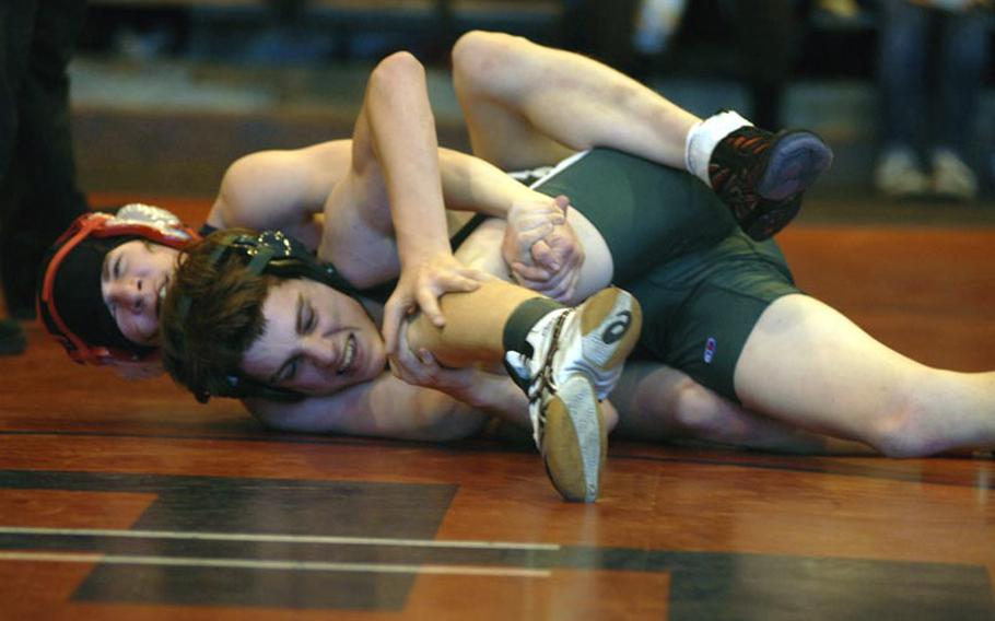 SHAPE's Steven Conkright tries to break free from Lakenheath's Marlon Fouse during a battle in the 126-pound weight class. Conkright, a freshman, defeated Fouse, a sophomore, by a score of 12-5.