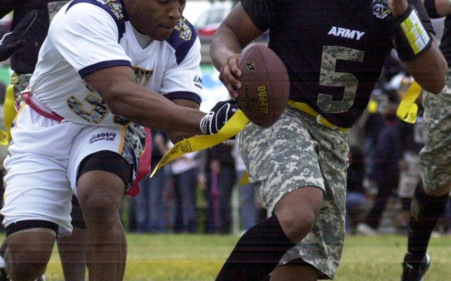Army quarterback Dean Werner tries to elude the tackle of Navy defender Torey Taylor during Saturday's 22nd Okinawa Army-Navy flag football game at Torii Field, Okinawa. Army rallied from a 21-12 deficit to beat Navy 25-21.