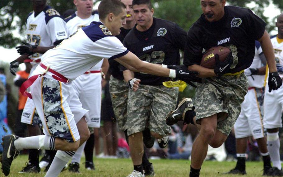 Army kick returner Antwyne Papion, right, tries to elude the tackle of Navy kicker Cody Wells during Saturday's 22nd Okinawa Army-Navy flag football game at Torii Field, Okinawa. Army rallied from a 21-12 deficit to beat Navy 25-21.