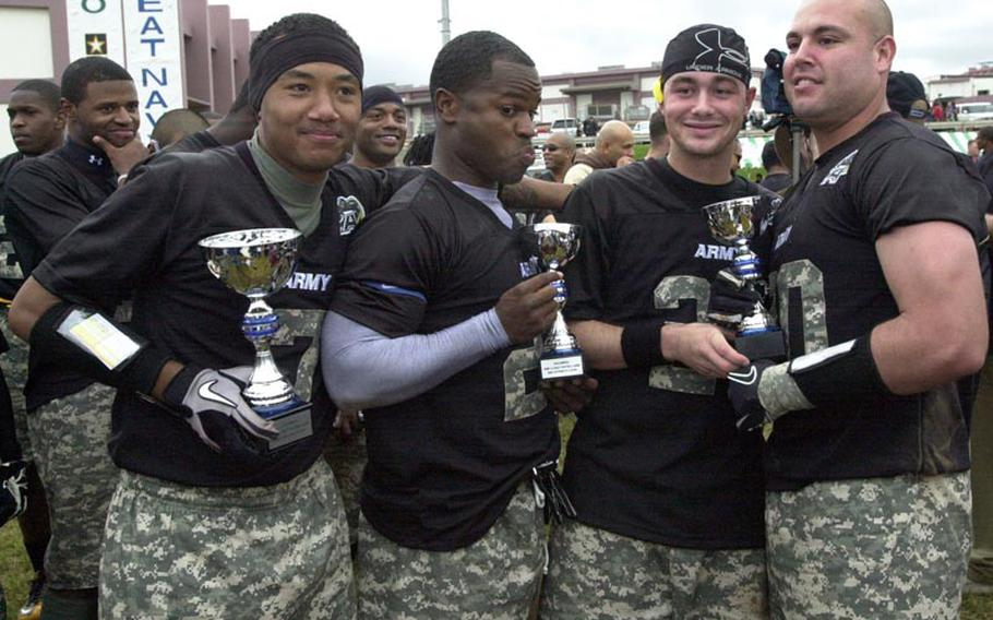 Army Most Valuable Player awardees Jamie Poole (overall MVP), Joseph Smallwood (offensive MVP) and Josh Harris and Michael Villalobos (co-defensive MVPs) celebrate with their hardware after Saturday's 22nd Okinawa Army-Navy flag football rivalry game at Torii Field, Okinawa. Army rallied from a 21-12 deficit to beat Navy 25-21.