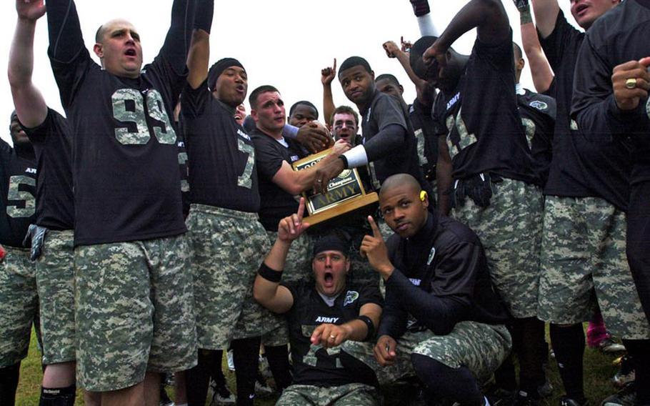 Army players and coaches celebrate with the Commander's Trophy after Saturday's 22nd Okinawa Army-Navy flag football game at Torii Field, Okinawa. Army rallied from a 21-12 deficit to beat Navy 25-21.