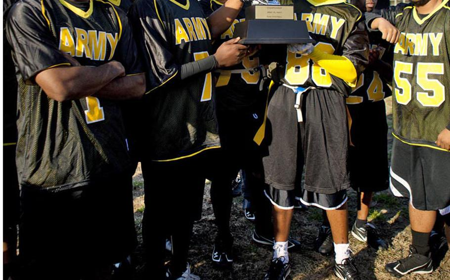 Army soldiers surround the championship trophy after Saturday's 10th Japan Army-Navy flag football game at Zama American High School, Japan. Army won 19-7, its second straight win, tying the series 5-5.