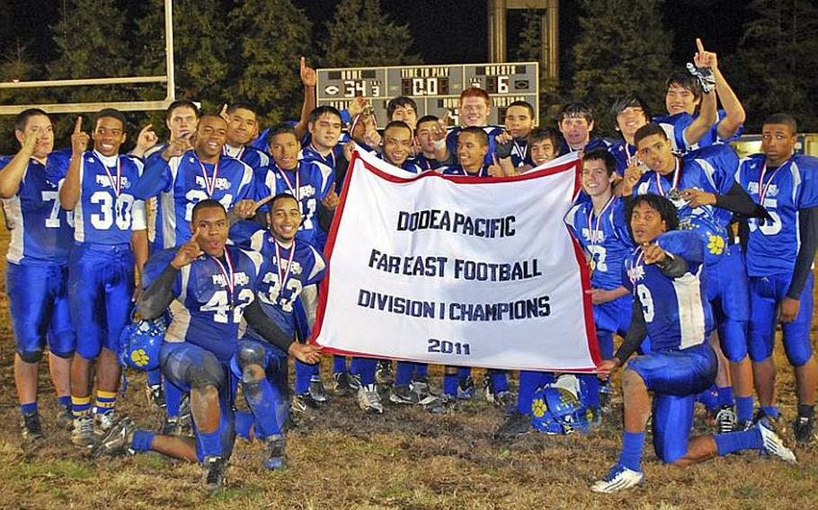 Yokota players celebrate with the banner after their 34-6 victory Saturday over Kubasaki in the Far East Division I championship game. It was Yokota's first D-I title in school history.