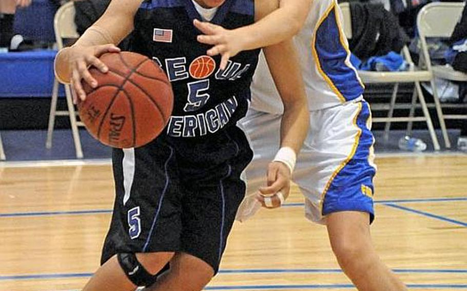 Seoul American senior Liz Gleaves dribbles past Liz Hardeman of Faith Academy during the championship game in the Far East High School Girls Division I Basketball Tournament in Guam. Seoul American beat Faith Academy for the second straight year 47-39. It was an unprecedented fourth straight D-I tournament title for Seoul American and fourth straight D-I tournament MVP award for Gleaves.