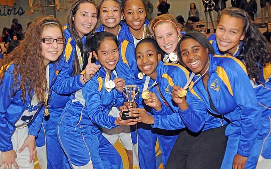 Yokota players celebrate with the championship trophy following Wednesday's championship game in the Yokota High School Christmas Classic girls basketball tournament in Japan. Yokota beat the Kadena Panthers 45-42 for the title.