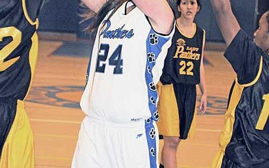 Yokota's Sarah Hamner puts up a shot between Kadena defenders Eisiah Lawson and Elva Harris during Wednesday's championship game in the Yokota High School Christmas Classic girls basketball tournament in Japan. Yokota beat Kadena 45-42.