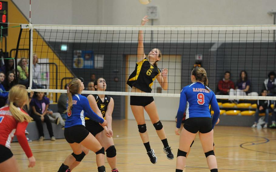 Patch's Rachel Hess hits the ball between the defense of Ramstein's Shannon Guffey, left, and Sarah Schiller in the the Division I final at the DODDS-Europe volleyball championships in Ramstein, Saturday. The Royals beat Patch 25-12, 25-14, 25-19 to defend their title.